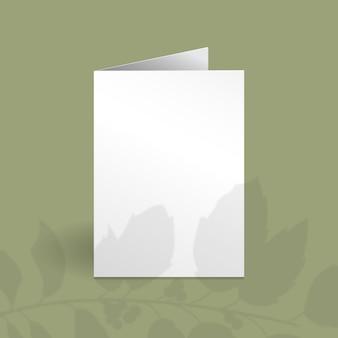 Weiße vertikale kartenschablone mit stechpalmenbeerenzweig mit blattüberlagerungsschatten.