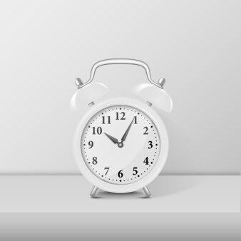 Weiße wecker-nahaufnahme, die auf weißem tisch steht. designvorlage