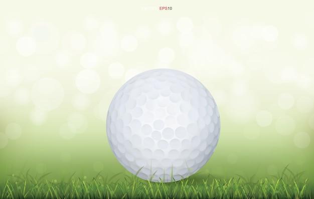 Weißer golfball im grünen grasfeld und im hellen verschwommenen bokehhintergrund