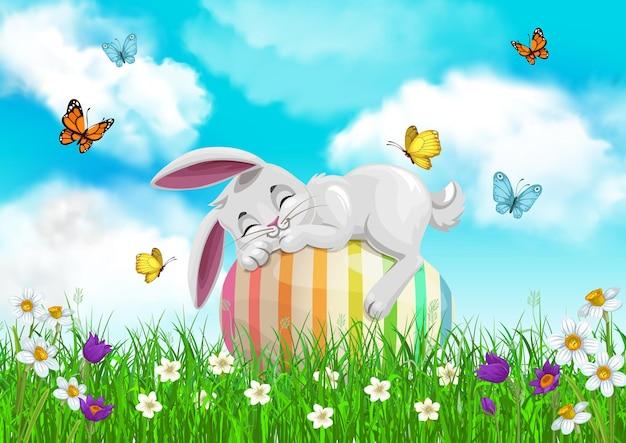 Weißer kaninchencharakter, der auf grünem gras des frühlingsfeldes mit blumen ruht