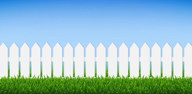 Weißer zaun mit grünem gras und blauem himmel