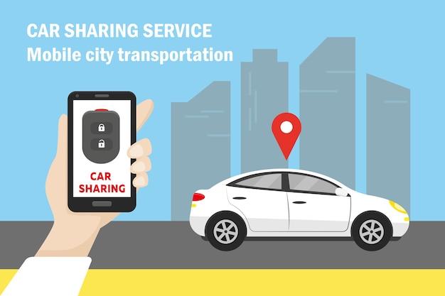 Weißes auto in der stadt und hand, die smartphone mit autoschlüssel auf dem bildschirm hält.