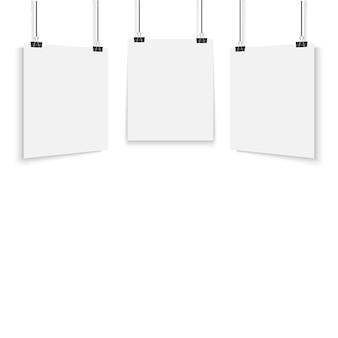 Weißes plakat, das mit binder hängt.