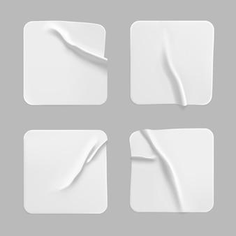 Weißes quadrat geklebte aufkleber gesetzt. leeres weißes quadratisches papier- oder plastikaufkleberetikett mit zerknittertem, zerknittertem effekt.