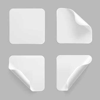 Weißes quadrat geklebte aufkleber mit gekräuselten ecken gesetzt. leeres weißes klebepapier oder plastikaufkleber mit zerknittertem, zerknittertem effekt.