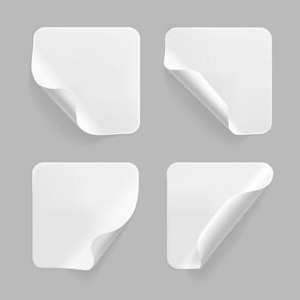 Weißes quadrat geklebte aufkleber mit gekräuselten ecken gesetzt. leeres weißes quadratisches papier- oder plastikaufkleberetikett mit zerknittertem, zerknittertem effekt.