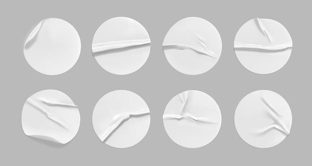 Weißes rundes zerknittertes aufkleberset. selbstklebendes weißes papier- oder plastikaufkleberetikett mit geklebtem, faltigem effekt auf grauem hintergrund. leere vorlagen eines etiketts oder preisschilder. 3d realistisch.