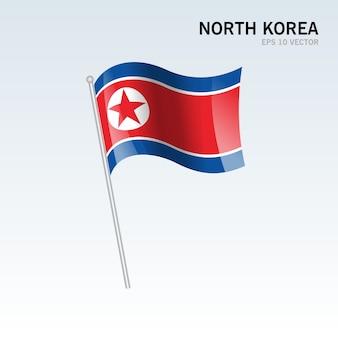 Wellenartig bewegende flagge nordkoreas lokalisiert auf grauem hintergrund