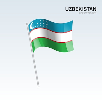 Wellenartig bewegende flagge usbekistans lokalisiert auf grauem hintergrund