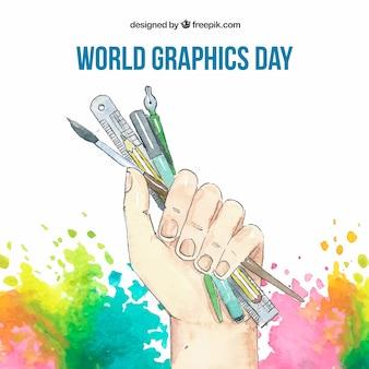 Weltgrafik-tageshintergrund mit der hand, die werkzeuge zum zeichnen in aquarellart hält