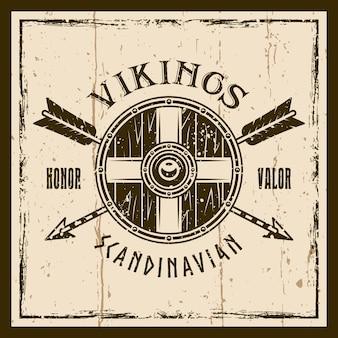 Wikinger-schild und gekreuzte pfeile vector braunes emblem, etikett, abzeichen oder t-shirt-druck auf hintergrund mit grunge-texturen