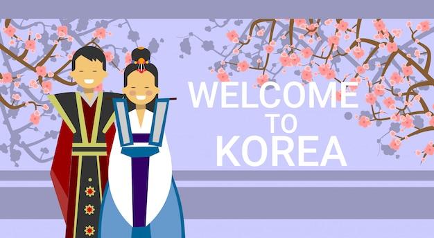 Willkommen in korea, koreanisches coupé in trachten über blühendem sakura-baum