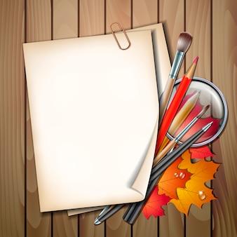 Willkommen zurück im schulischen hintergrund. schulgegenstände und elemente. papierblatt mit herbstlaub, stiften, bleistiften, pinseln und lupe auf holztisch