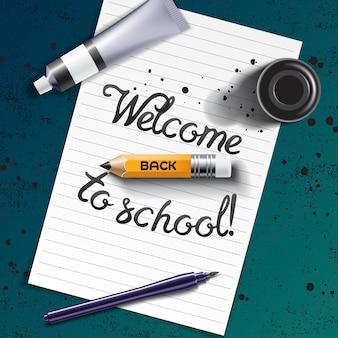 Willkommen zurück in der schule handgezeichnete schrift mit kalligraphiemodell mit pinselstift, scharfem bleistift, farbtube und schwarzer tintenflasche auf dem raum aus weißem blatt papier und grunge-kreidetafel