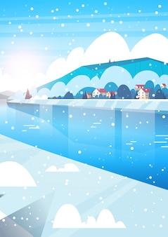 Winter-natur-landschaftshäuser auf gefrorenen fluss-hügeln und fallendem schnee
