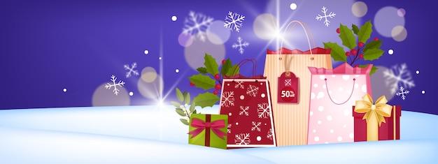 Winterferien weihnachts- und neujahrsverkaufsbanner mit einkaufstüten, geschenkboxen, schneeverwehungen
