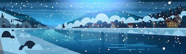 Winterlandschaft der nacht im kleinen dorf am ufer des gefrorenen flusses und der bedeckten gebirgshügel