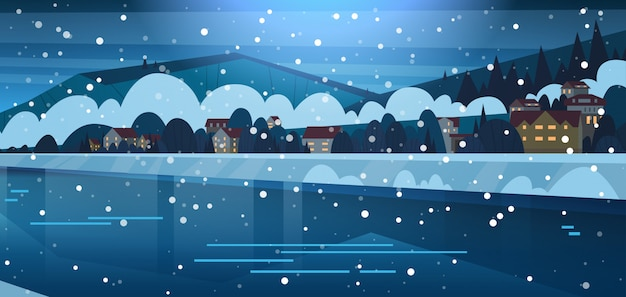 Winterlandschaft von kleinen dorfhäusern auf den banken des gefrorenen flusses und der bedeckten gebirgshügel