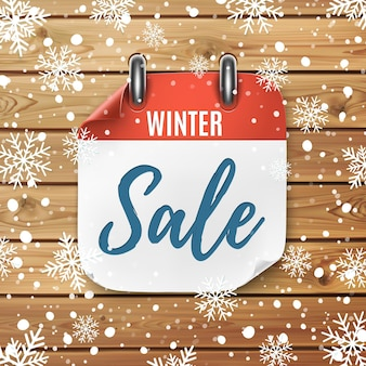 Winterverkauf. realistisches kalendersymbol. holzhintergrund mit schnee und schneeflocken.