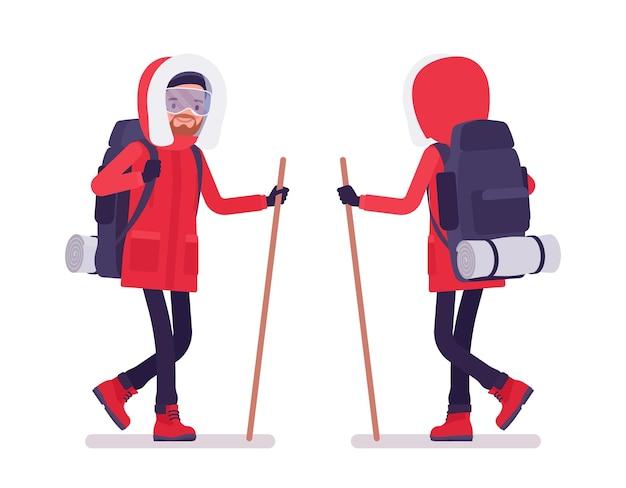 Winterwandernder mann, der mit einem stock geht