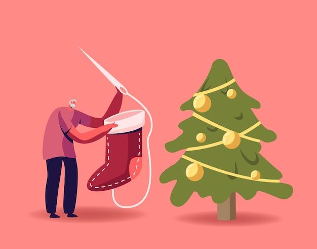 Winzige ältere männliche figur, die riesige festliche socke in der nähe von geschmücktem weihnachtsbaum näht