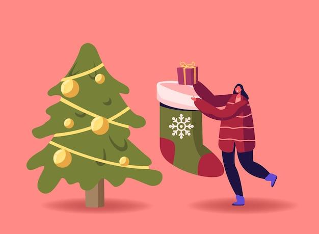 Winzige weibliche figur mit riesiger festlicher weihnachtssocke mit geschenkbox. mädchen tragen geschenk nahe tannenbaum