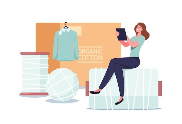 Winzige weibliche figur sitzt auf einer riesigen fadenspule und einem hemd aus 100 prozent baumwolle, das am kleiderbügel hängt