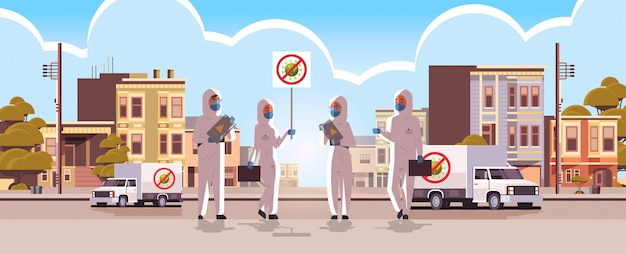 Wissenschaftler in hazmat-anzügen halten stop coronavirus banner desinfektion von epidemievirus leere stadtstraße wuhan pandemie gesundheitsrisiko in voller länge horizontal