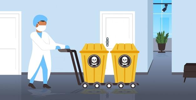 Wissenschaftler in maske schiebt biogefährdungsbehälter mit schädel und knochen auf wagenstopp coronavirus-epidemie mers-cov-konzept wuhan 2019-ncov pandemie gesundheitsrisiko in voller länge horizontal