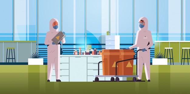 Wissenschaftler in schutzanzügen tragen fässer mit warnzeichen grippe ausbruch china pathogen quarantäne coronavirus konzept labor innenraum horizontal