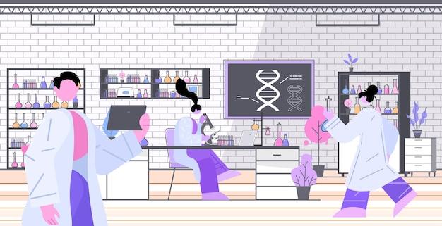 Wissenschaftlerteam, das mit dna-forschern zusammenarbeitet, die experimente im labor dna-testen des genetischen diagnosekonzepts durchführen testing