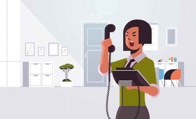 Wütende geschäftsfrau, die am telefon schreit