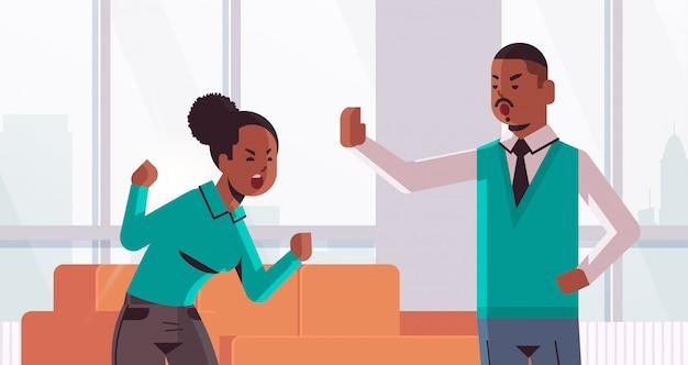 Wütendes paar, das argumentiert, sich gegenseitig zu beschuldigen beleidigten afroamerikanermann, der stoppgestenfrau schreit, die uneinigkeit konfliktkonzept modernes wohnzimmerinnenporträt horizontal zeigt