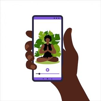 Yoga online-konzept. frau, die yoga-übung zu hause mit afrikanischem online-lehrer auf handy macht. wellness und gesunder lebensstil zu hause. frau, die yogaübungen macht. abbildung in wohnung.