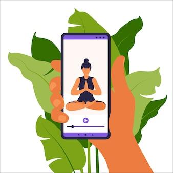 Yoga online-konzept. frau, die yoga-übung zu hause mit online-lehrer auf handy macht. wellness und gesunder lebensstil zu hause. frau, die yogaübungen macht.
