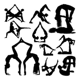 Yoga-paar stellt silhouetten auf.