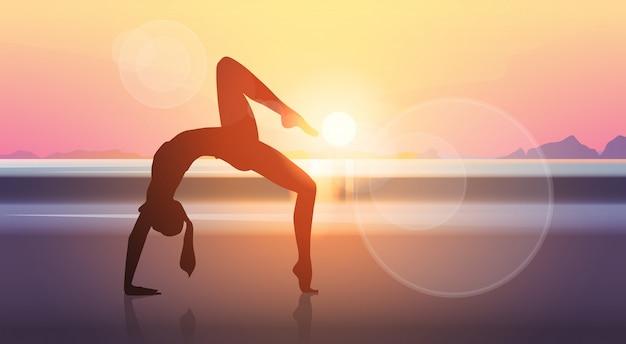 Yoga-sport-eignungs-frauen-übungs-training silhouettiert mädchen-seesonnenuntergang-hintergrund