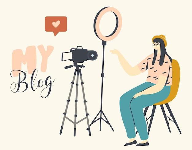Young girl vlogger character shooting vlog machen sie eine überprüfung der videoaufnahme, die im raum mit professioneller lichtausrüstung sitzt