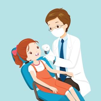 Zahnarzt, der niedlichen mädchenpatienten auf zahnarztstuhl behandelt