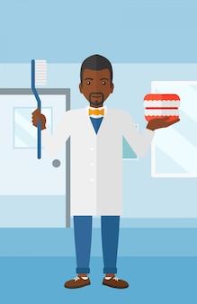 Zahnarzt mit zahnmedizinischem kiefermodell und zahnbürste.
