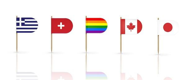 Zahnstocherflaggen der länder. griechenland, schweiz, kanada, japan und lgbt-regenbogenwimpel auf spitzen holzstäbchen