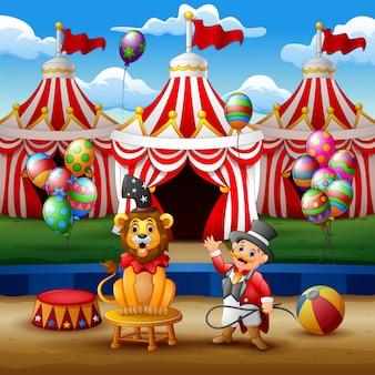 Zirkustrainer führt einen trick zusammen mit einem löwen in der arena durch