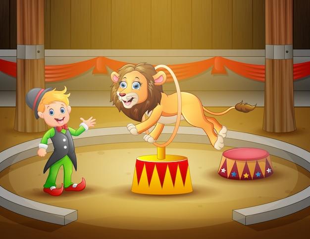 Zirkustrainer führt einen trick zusammen mit löwen in der arena durch