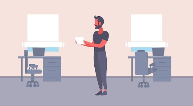 Zufälliger geschäftsmannlesepapierdokumenten-vertragsmann, der horizontale innenebene des modernen arbeitsplatzbüros der geschäftskorrespondenz männlichen arbeitskraft hält