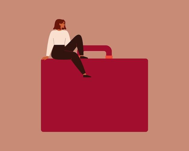 Zuversichtlich junge geschäftsfrau sitzt auf großer roter aktentasche. starke unternehmerin mit handtasche.