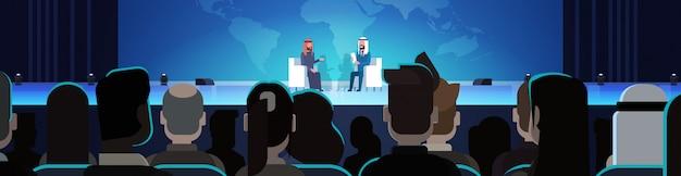 Zwei arabische geschäftsleute oder politiker auf konferenz oder debatten-sitzungs-interview sprechend über weltkarte vor horizontaler illustration des großen publikums