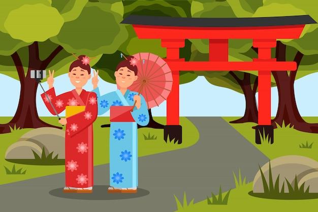 Zwei asiatische frauen machen selfie vor dem japanischen torii-tor. junge mädchen in kimonos. flache landschaft mit grünen bäumen, gras und weg