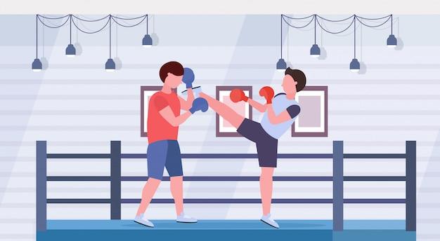 Zwei boxer, die kickboxübungen trainieren, üben kämpfer in handschuhen, die zusammen modernen kampfklubringarena-innenkonzept des gesunden lebensstils flach horizontal in voller länge üben