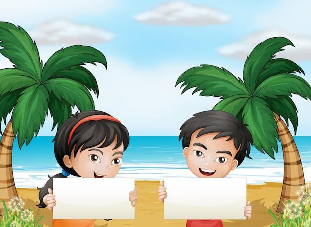 Zwei entzückende kinder am strand mit leeren schildern