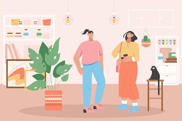 Zwei frauen treffen sich im kunstgeschäft oder im atelier. junge freundinnen stehen, reden, kaffee trinken. innenarchitektur der künstlerwerkstatt.